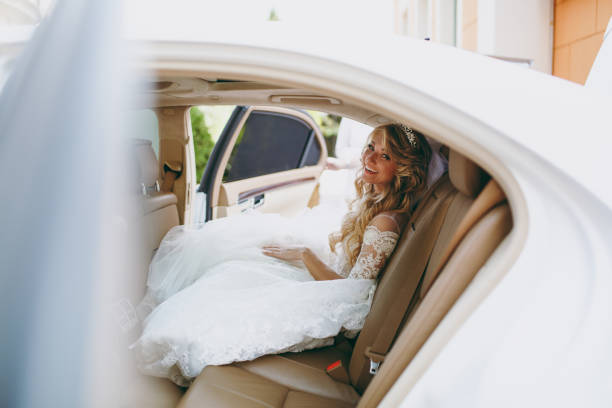 Beautiful blond bride gets into the car stock photo