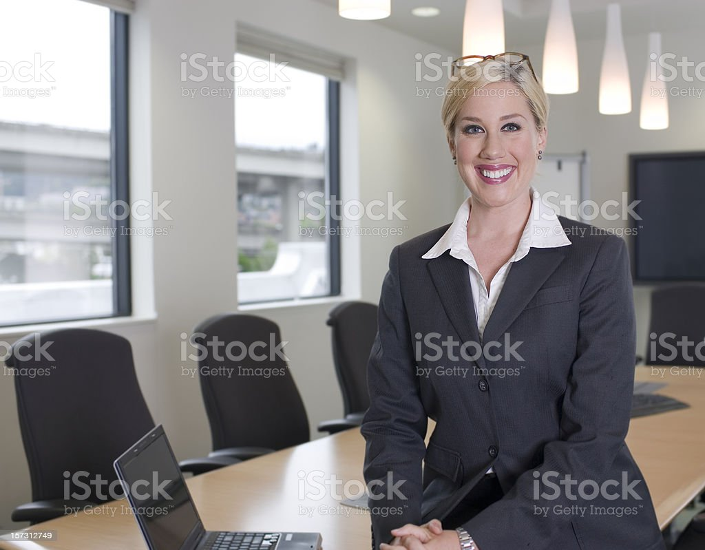 Beautiful Blond Businesswoman in Meeting Room with Laptop, Copy Space royalty-free stock photo