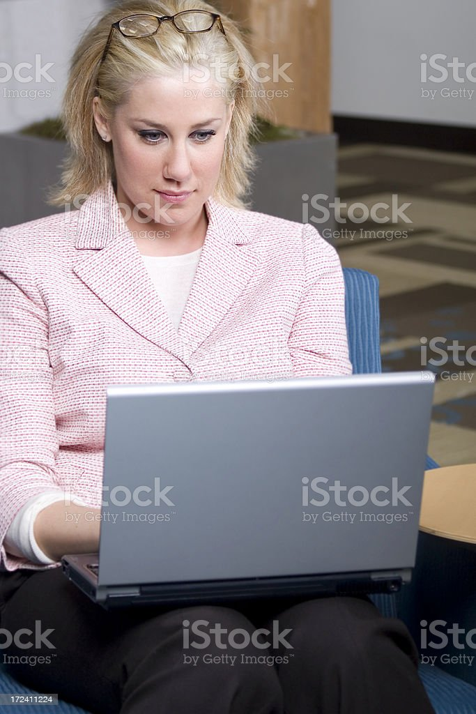 Beautiful Blond Businesswoman Using Laptop in Office Lobby, Copy Space royalty-free stock photo