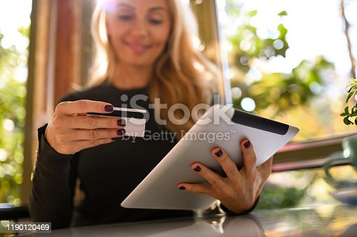 Beautiful blond caucasian woman using her credit card for online shopping on her tablet. She's smiling, happy to make an online purchase. She's sitting by the window in a cafe surrounded by trees.