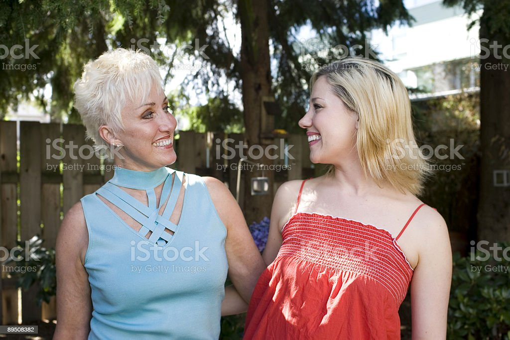 Beautiful Blond Daughter and Mother Looking at Eachother Smiling royalty-free stock photo