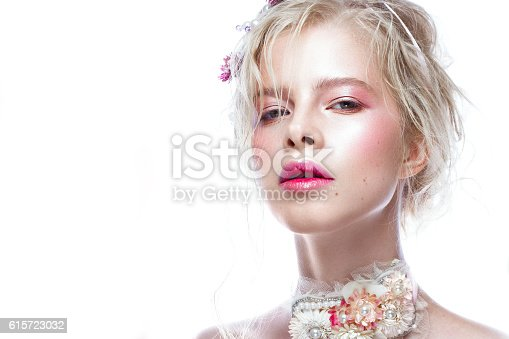 istock Beautiful blond fashion girl with flowers on neck and in 615723032