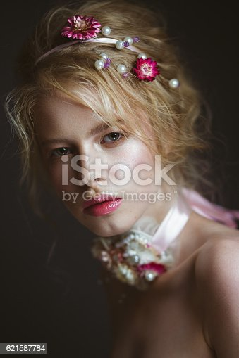 istock Beautiful blond fashion girl with flowers on neck and in 621587784