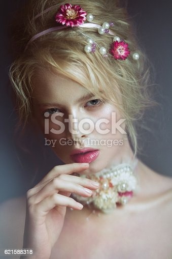 istock Beautiful blond fashion girl with flowers on neck and in 621588318
