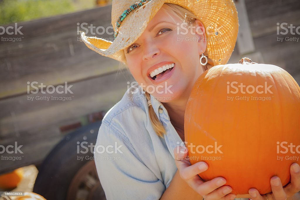 Beautiful Blond Female Rancher Wearing Cowboy Hat Holds a Pumpkin royalty-free stock photo