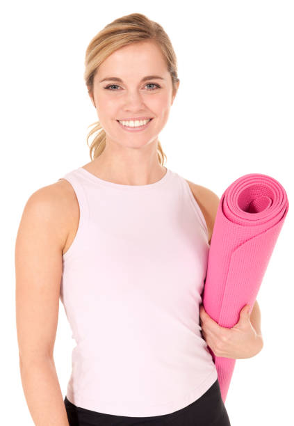 Beautiful blond female with pink yoga mat smiling bright Young woman with yoga mat isolated on white background yoga instructor stock pictures, royalty-free photos & images