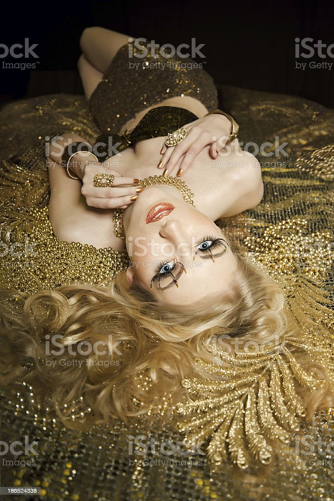 Beautiful blond girl /fashion model on bed of gold royalty-free stock photo