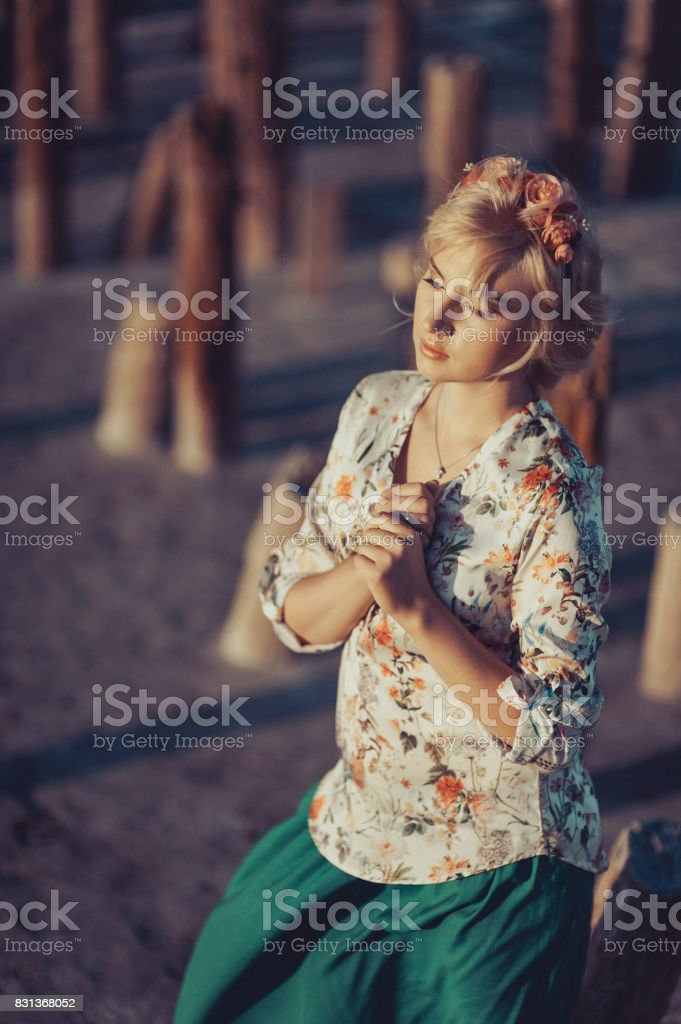 Beautiful blond girl in a wreath for a walk near the bricks stock photo