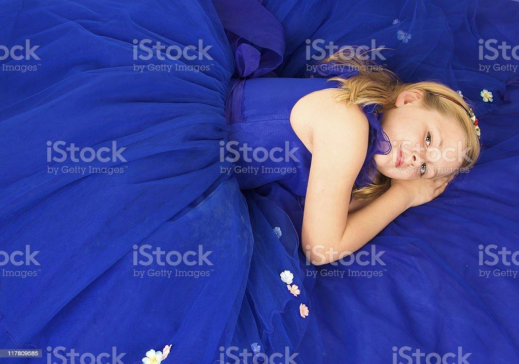 Hermosa chica rubia acostado en un vestido azul marino - foto de stock