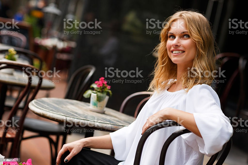 Beautiful blond girl sitting in street cafe on summer day royalty-free stock photo