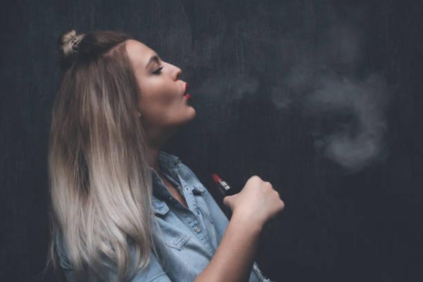 Fotos de Pelo Rubio Ceniza e Imágenes de Stock. Hermosa chica rubia fuma  vape - foto de stock 03699e807a14