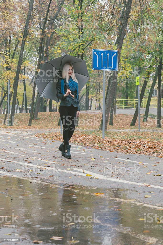Beautiful blond girl with umbrella walking down the street on rainy...