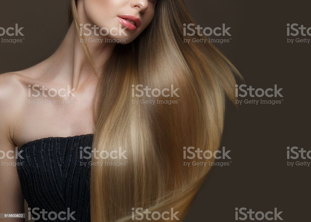 Beautiful blond girl with a perfectly smooth hair, classic make-up. Beauty face stock photo