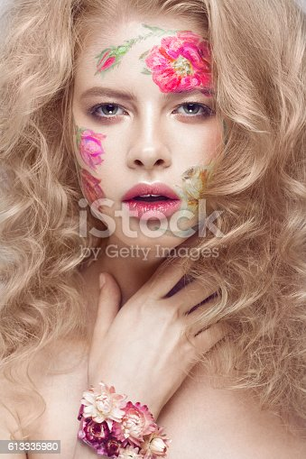 istock Beautiful blond girl with curls and a floral pattern on 613335980