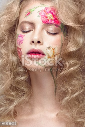istock Beautiful blond girl with curls and a floral pattern on 613336072