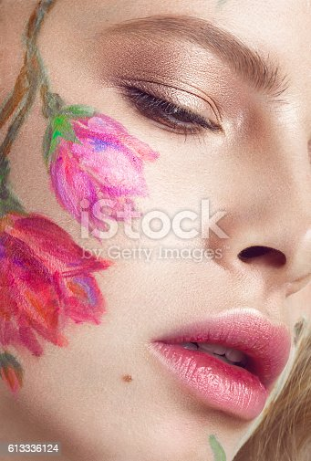 istock Beautiful blond girl with curls and a floral pattern on 613336124