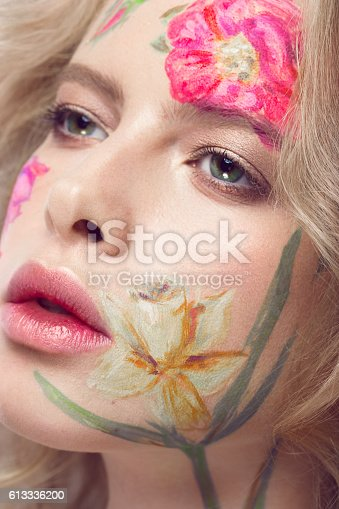 istock Beautiful blond girl with curls and a floral pattern on 613336200