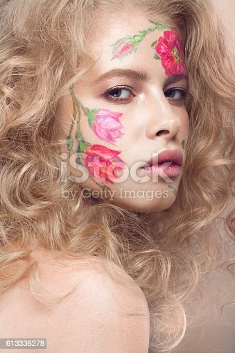 istock Beautiful blond girl with curls and a floral pattern on 613336278