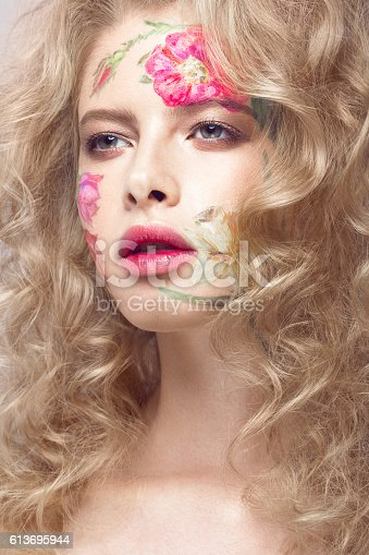 istock Beautiful blond girl with curls and a floral pattern on 613695944