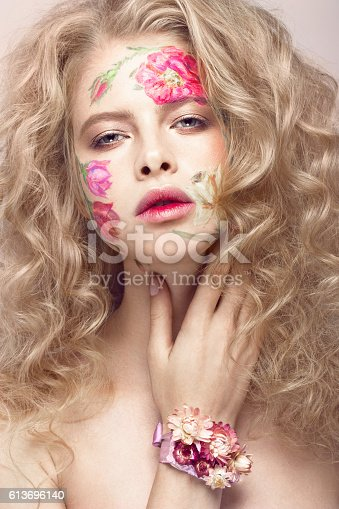 istock Beautiful blond girl with curls and a floral pattern on 613696140