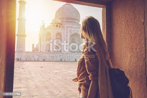 Young woman wandering around the famous Taj Mahal at sunset, Agra, India. People travel Asia concept