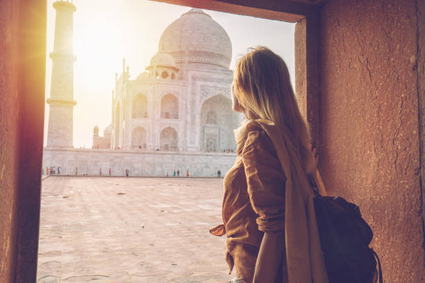 Beautiful blond hair girl contemplating sunrise at the Taj Mahal in India stock photo