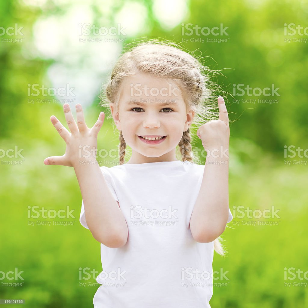 Beautiful blond little girl showing six fingers (her age) stock photo