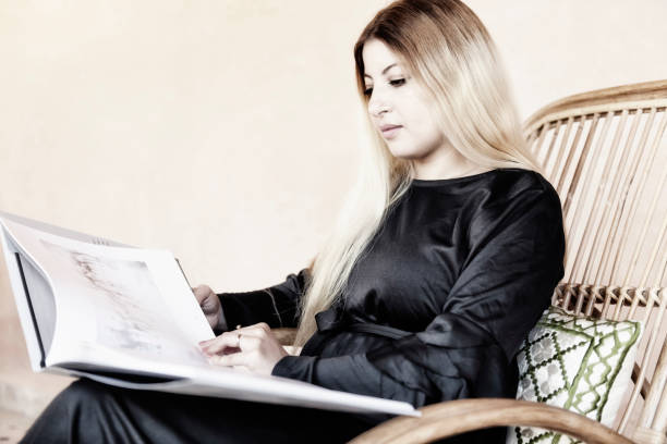 A beautiful blond Moroccan Arab woman enjoys a photography art coffee-table book. stock photo