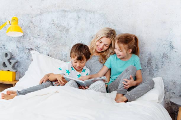 Schöne blonde Mutter ist ihren Kindern eine Geschichte lesen. – Foto