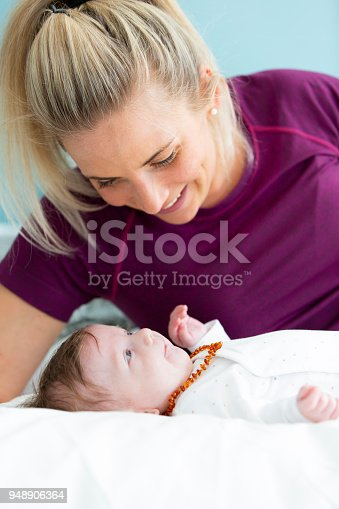 istock beautiful blond mother with her 3 month old baby wearing a amber necklace 948906364
