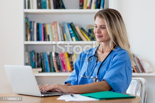 Beautiful blond nurse working at computer at hospital