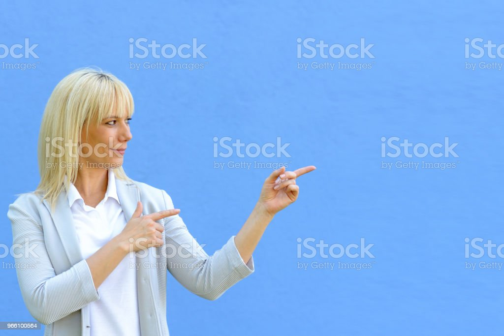 Beautiful blond pointing at copy space - Royalty-free Adulto Foto de stock