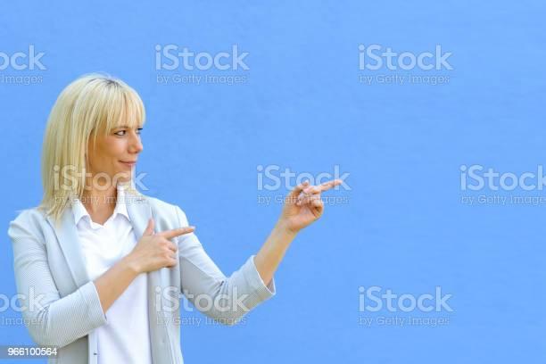 Beautiful Blond Pointing At Copy Space - Fotografias de stock e mais imagens de Adulto