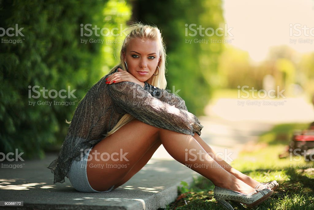 Beautiful blond sitting on a street royalty-free stock photo