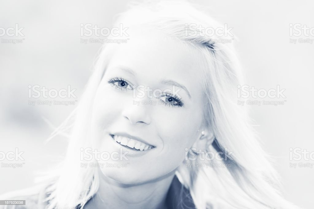 beautiful blond smiling girl portrait, blue toned royalty-free stock photo