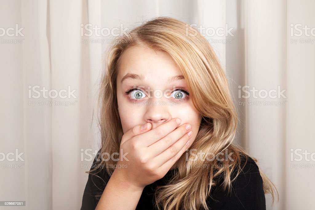 Beautiful blond surprised girl opened her eyes wide stock photo