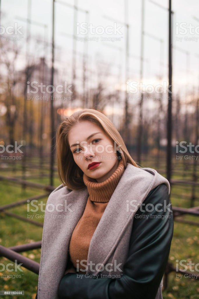 Beautiful blond teen standing up against grass in the background with autumn outfit stock photo