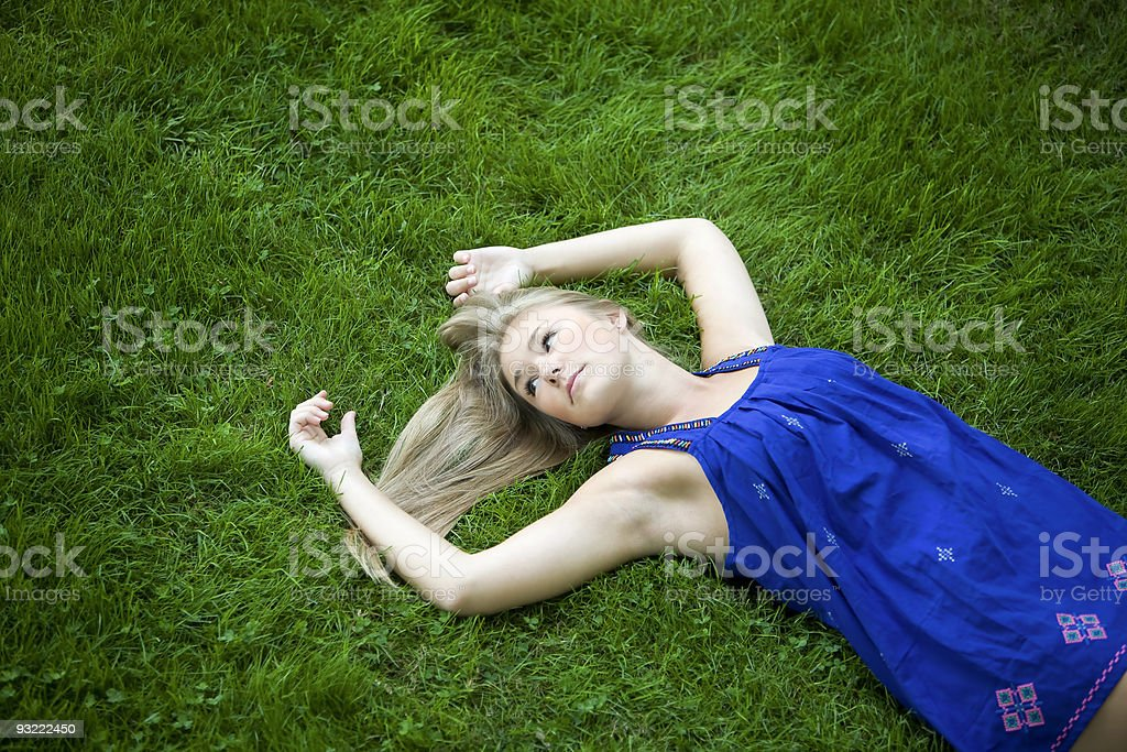 Beautiful Blond Teenage Girl Lying on Green Grass royalty-free stock photo