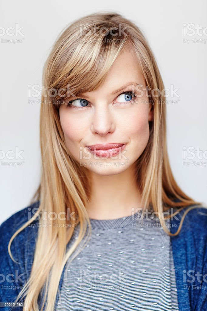 Beautiful blond thinking in studio, smiling stock photo