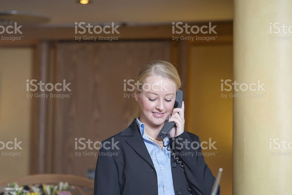 Beautiful blond woman answering a telephone royalty-free stock photo