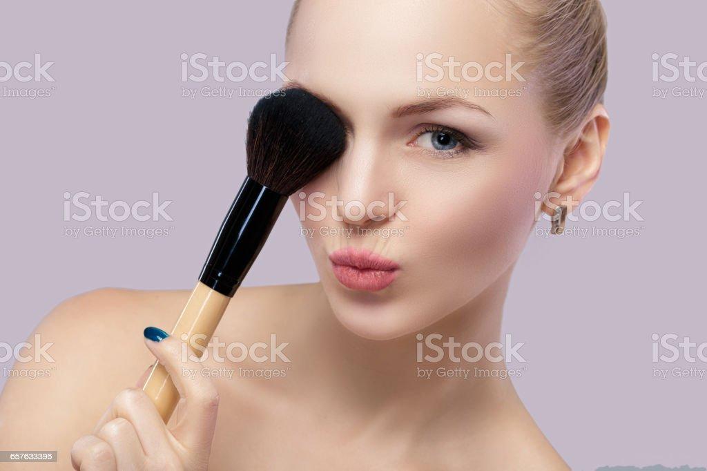 hermosa mujer rubia con pincel de maquillaje sobre un fondo gris. - foto de stock