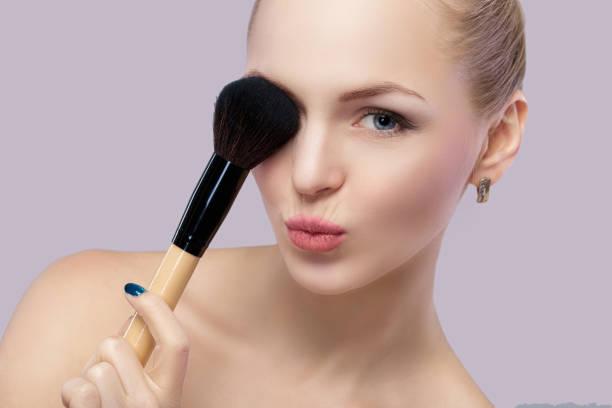 beautiful blond woman holding makeup brush on a gray background. stock photo