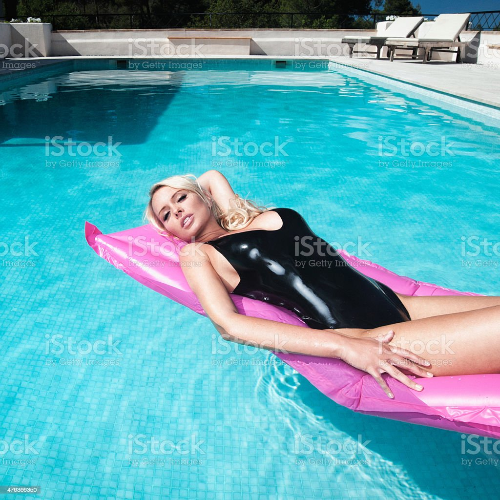 Beautiful Blond Woman in a Black Latex Swimsuit, Pin-Up Pose stock photo