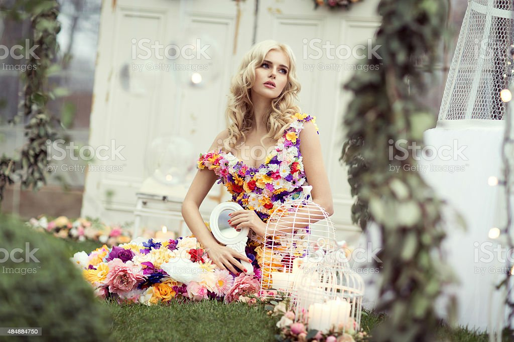 Beautiful blond woman in a dress of flowers sitting stock photo