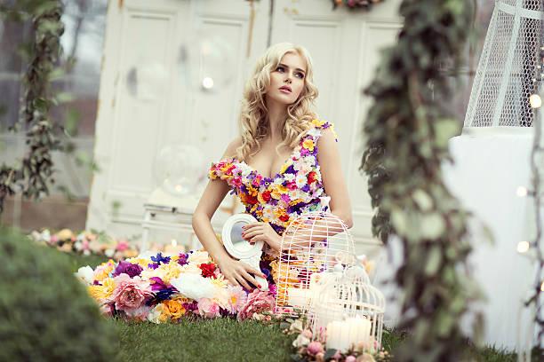 schöne blonde frau im kleid blumen-sitzbereich - tortenfiguren stock-fotos und bilder