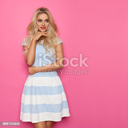 Blond beautiful woman in white and blue dress is posing and looking away. Three quarter length studio shot on pink background.