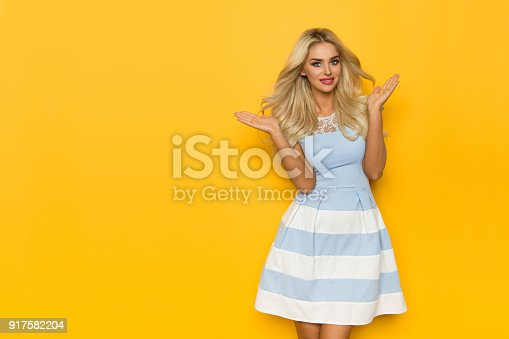 Blond beautiful woman in white and blue dress is posing with hands raised, smiling and looking at camera. Three quarter length studio shot on yellow background.