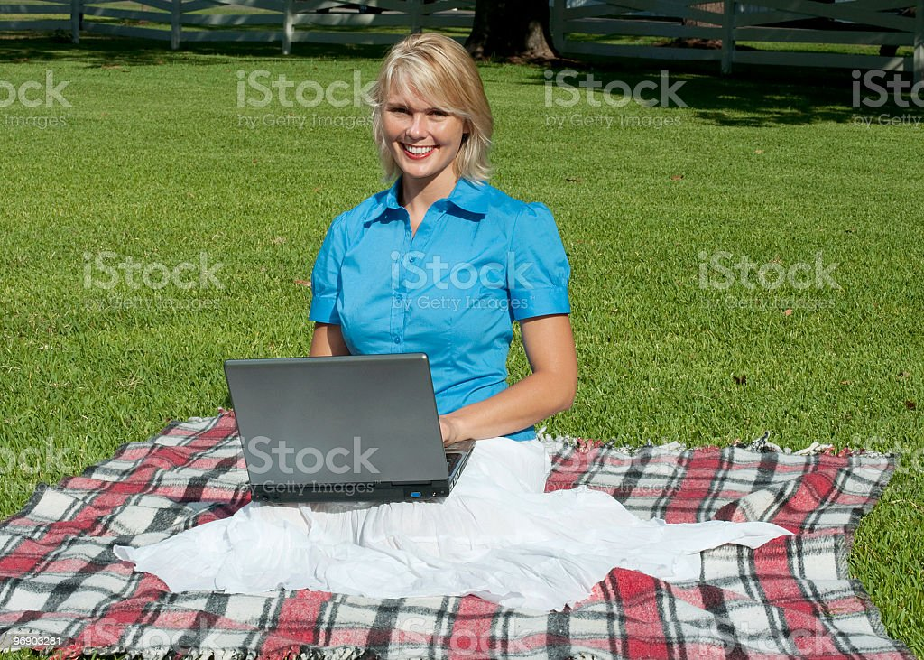 Beautiful blond woman in blue sitting outdoors with laptop computer royalty-free stock photo