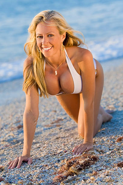 beautiful blond woman in white bikini crawling on a beach - busty women in bikinis stock pictures, royalty-free photos & images