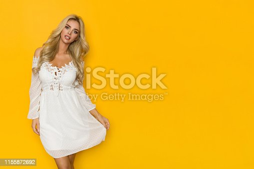 Beautiful blond woman is posing in white lace mini dress. Three quarter length studio shot on yellow background.